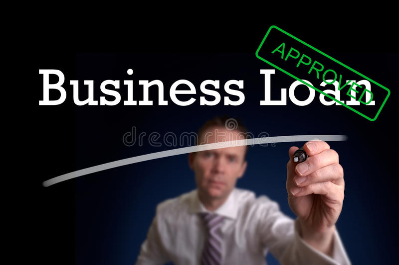 Business Loan. An underwriter writing Business Loan approved on a screen royalty free stock image