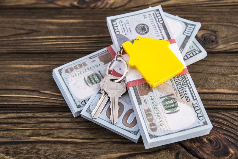 Business loans for real estate concept, keys and yellow symbol house keychain. On money packs dollar stock photos