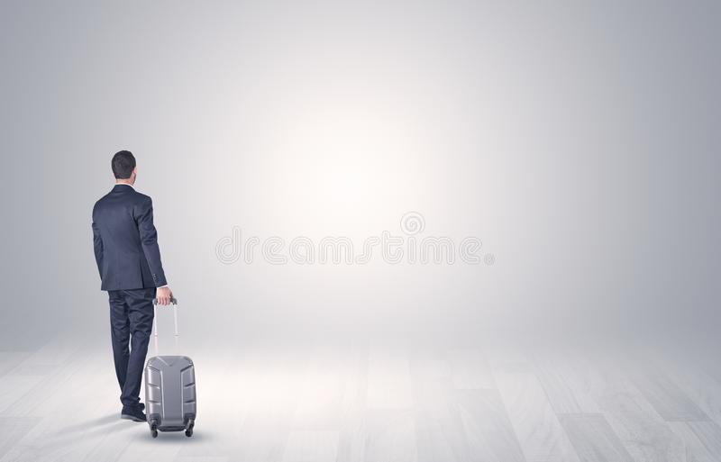 Business with luggage in a boundless space. Young businessman in a white boundless space walking with back and luggage on his hand stock photos