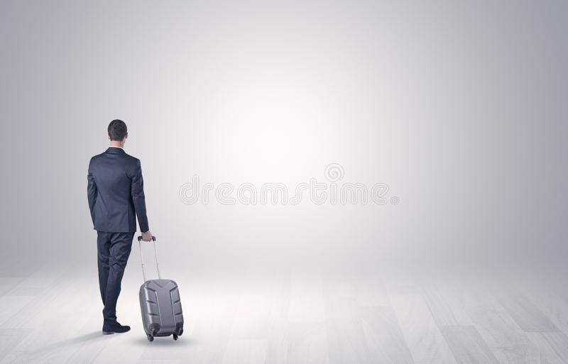 Business with luggage in a boundless space. Young businessman in a white boundless space walking with back and luggage on his hand stock image