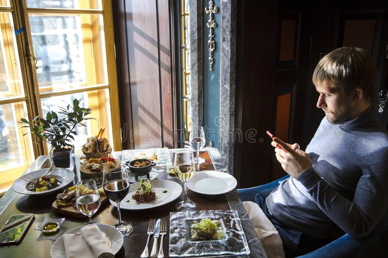 Contemporary young man in elegant restaurant using cell phone stock images