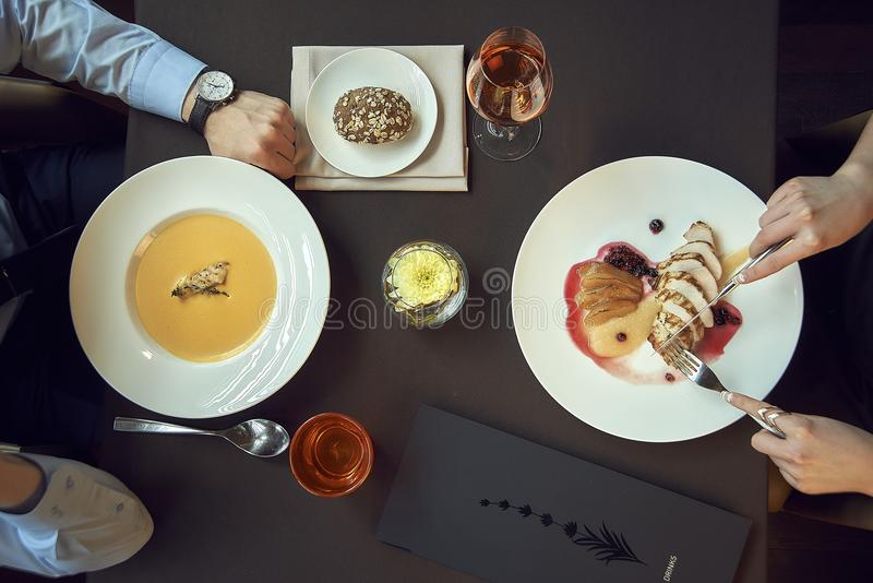 Business lunch or dinner in a restaurant. hands on table, dishes like soup and meat, eating. top view stock images