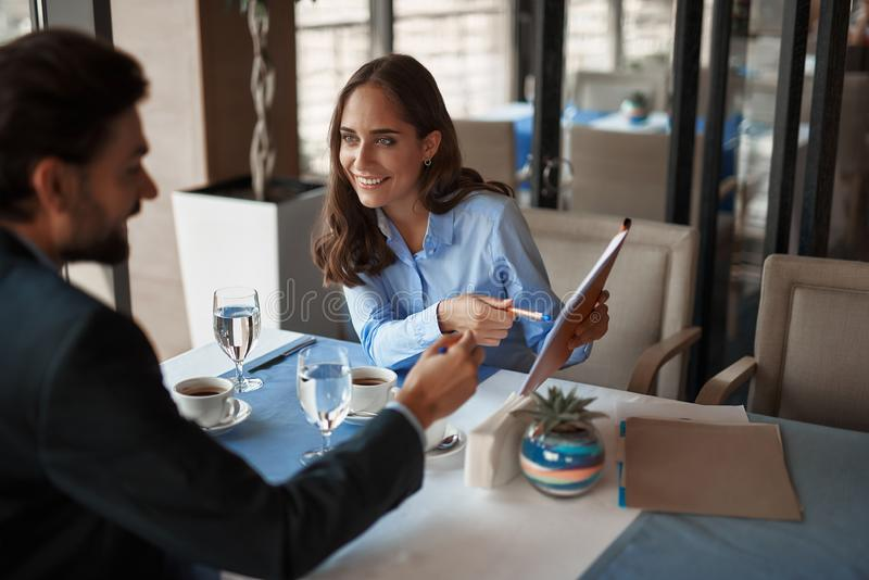 Man and woman are discussing business plans. Business lunch in friendly atmosphere. Portrait of young smiling businesswoman explaining work project to her male royalty free stock photo