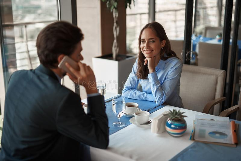 Two colleagues having business lunch in restaurant. Business lunch in friendly atmosphere. Portrait of young smiling businesswoman sitting with men in restaurant stock images