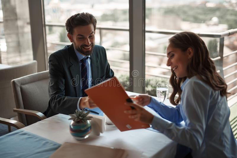 Man and woman spending time in restaurant. Business lunch in friendly atmosphere. Portrait of young smiling male and female colleagues discussing work while royalty free stock image