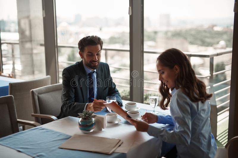 Man and woman discussing business tasks in restaurant. Business lunch in friendly atmosphere. Portrait of young smiling male and female work partners signing stock photo