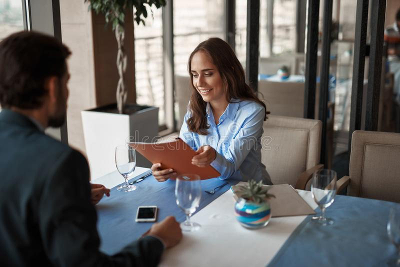 Two colleagues having business lunch in restaurant. Business lunch in friendly atmosphere. Waist up portrait of young men and women sitting in restaurant and stock photography