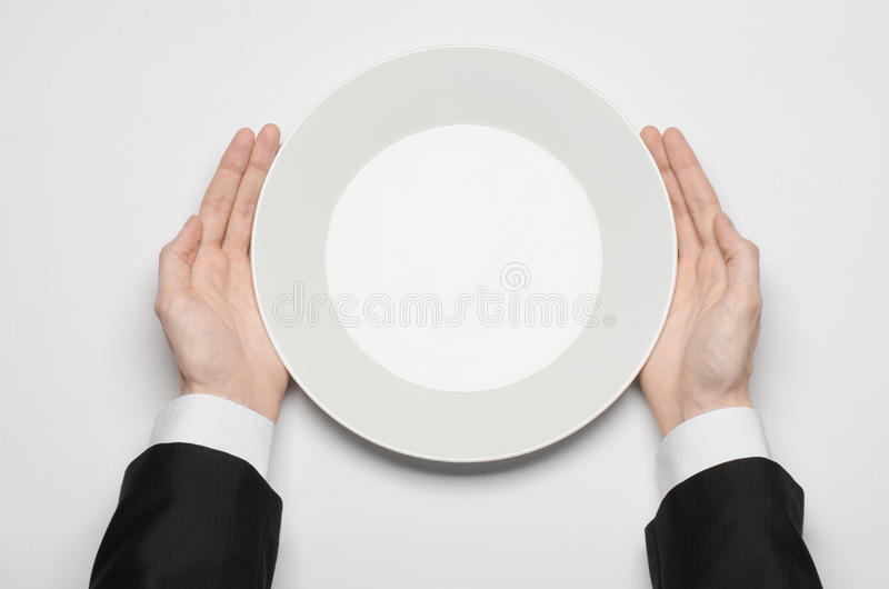 Business lunch and healthy food theme: man's hand in a black suit holding a white empty plate and shows finger gesture on an royalty free stock photos
