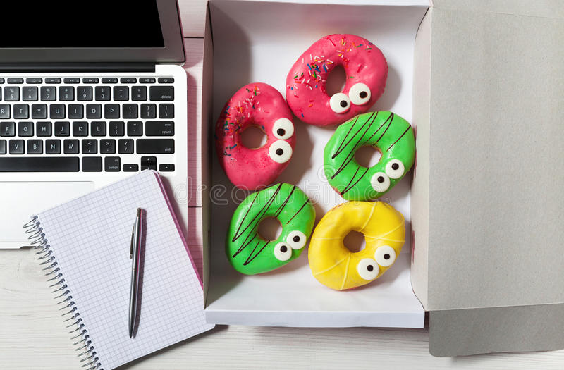 Business lunch snack in office, glazed donuts box top view. Snack time in office. Colorful glazed donuts with funny eyes near computer keyboard and notepad with royalty free stock photos