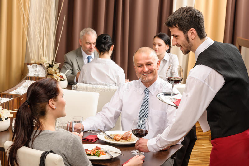 Business lunch waiter serving red wine royalty free stock images