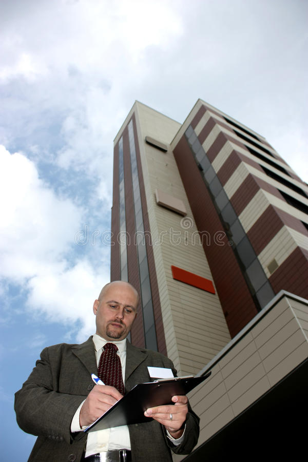 Business man. A business man filling in a checklist in front of an office building isolated on sky royalty free stock images