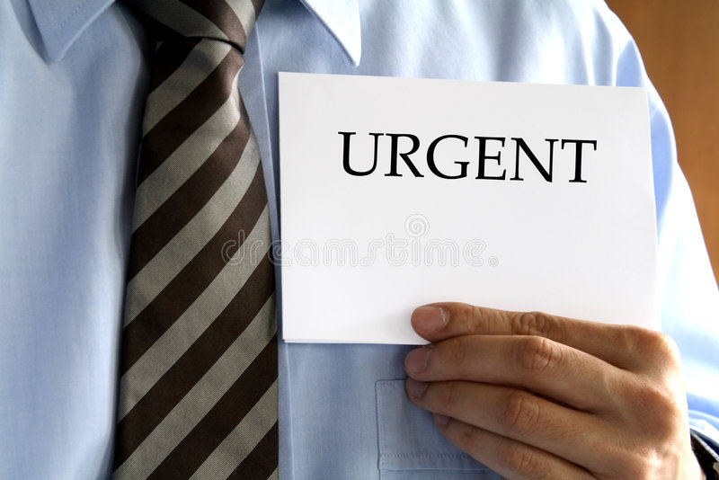 Business Man. In formal attire holding up a piece of paper that says Urgent royalty free stock image