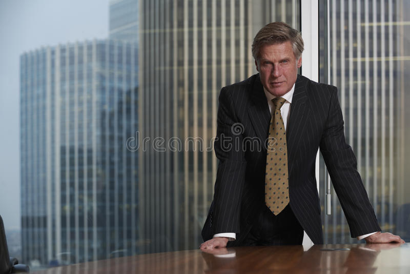 Business Man. Leaning on table in boardroom looking at camera royalty free stock photography