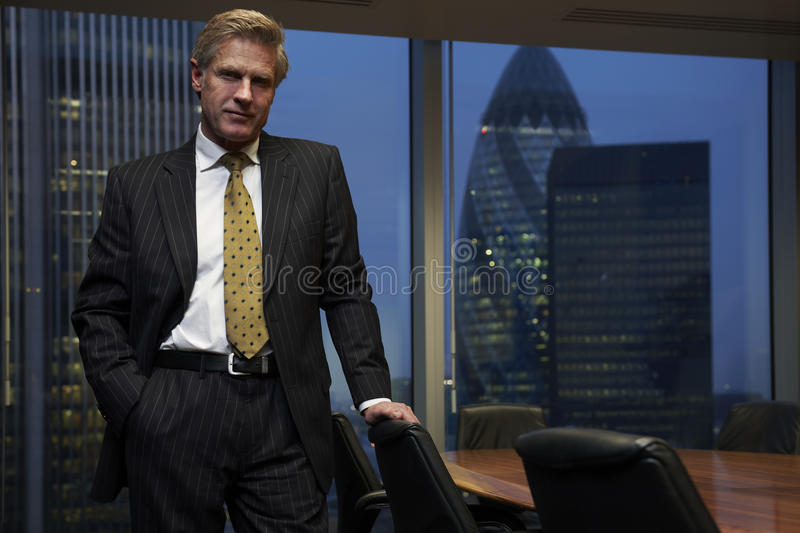 Business Man. Leaning on chair in boardroom looking at camera royalty free stock photography
