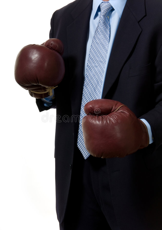 Business man. In suit with boxing gloves in front of white. Symbol of difficulty of buisness stock images