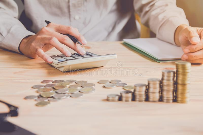 Business man or  accountant in gray shirt holding pen working on accounts and using  calculator and writing on desk stock photos