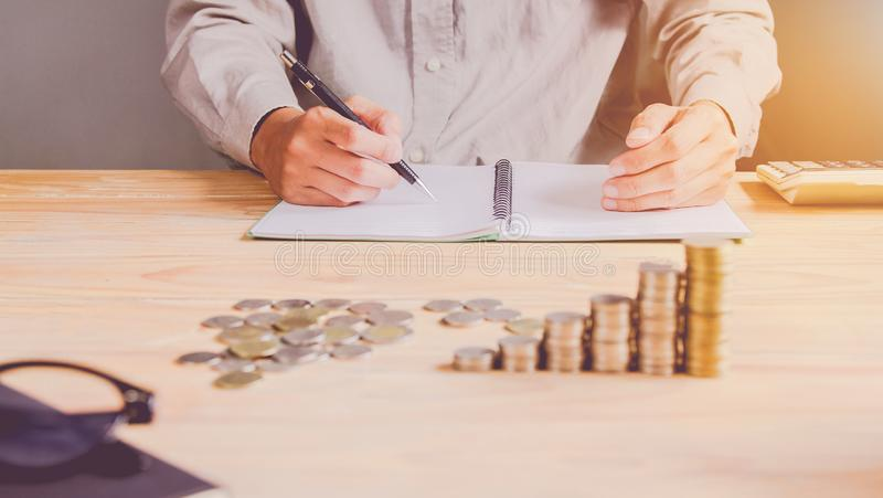 Business man or  accountant in gray shirt holding pen working on accounts and using  calculator and writing on paper stock image