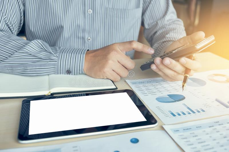 Business man or accountant working Financial investment on calculator with calculate Analyze business and market growth on. Financial document data graph and royalty free stock photography
