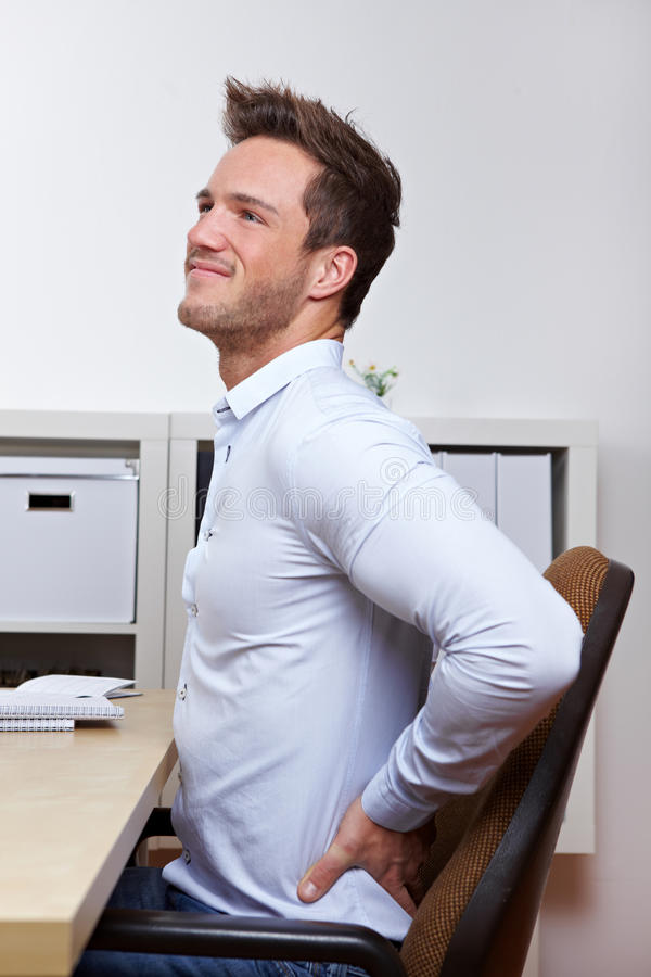 Business man with back pain. In office chair at desk royalty free stock images
