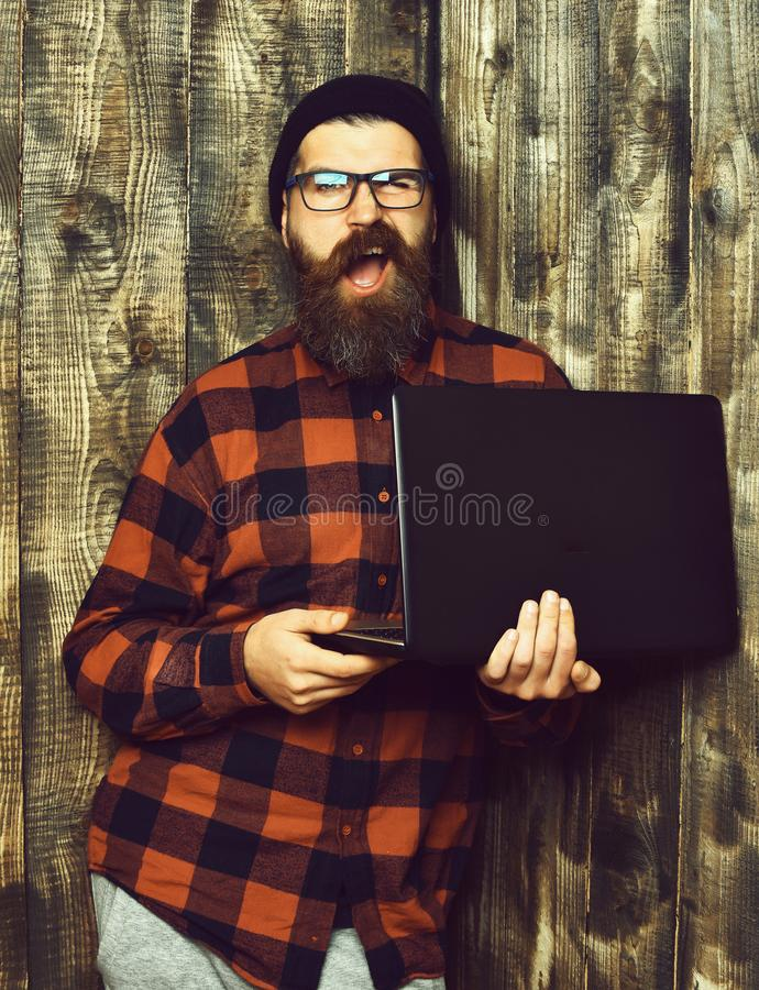 Business man. Bearded brutal caucasian hipster holding laptop. Business man. Bearded man, long beard. Brutal caucasian unshaven hipster holding laptop in red stock images