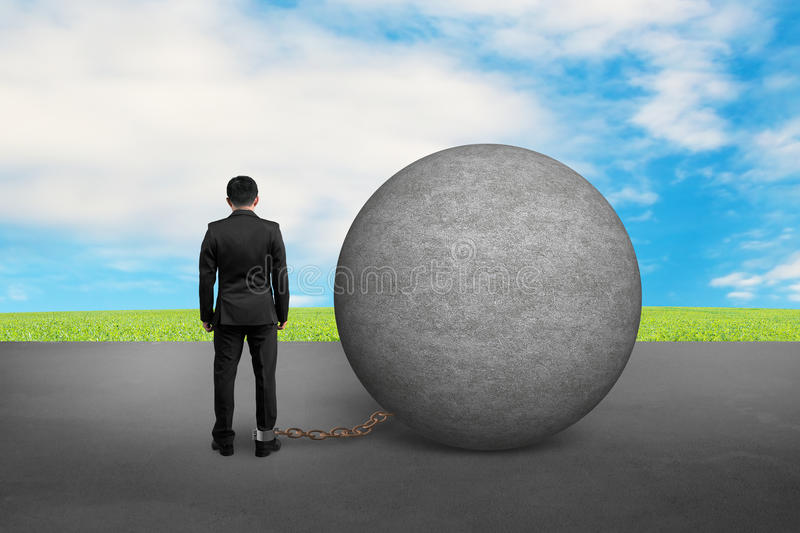 Business man being trapped with concrete ball stock photography