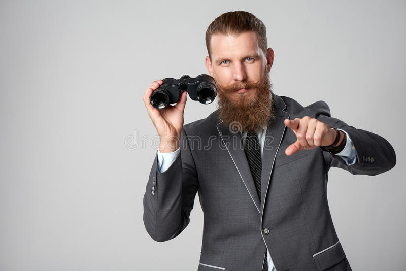 Business man with binoculars. Closeup portrait of bearded hipster business man in suit holding binoculars and pointing at camera royalty free stock photography