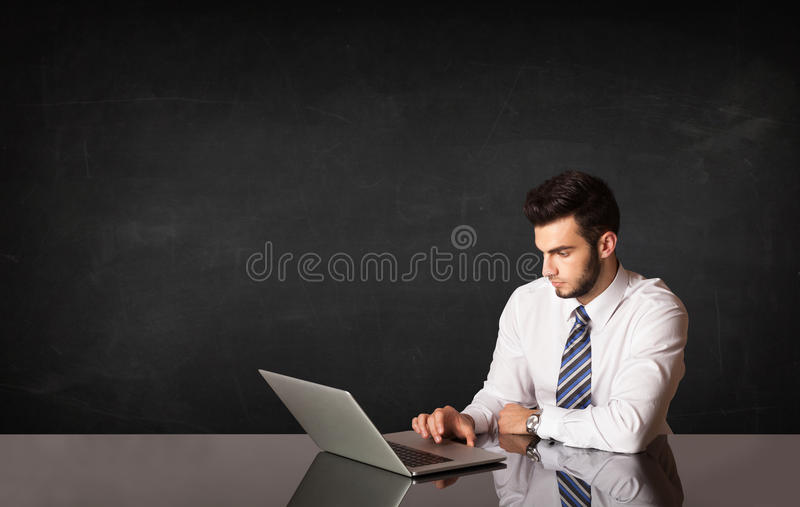 Business man with black background. Business man sitting at black table with a laptop on black background royalty free stock photo