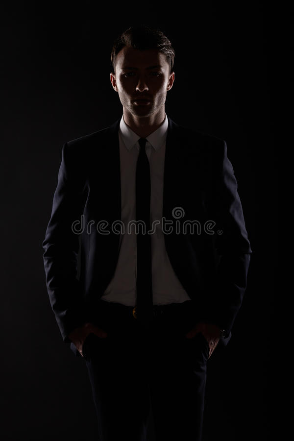 Business man in black suite, backlight stock photography