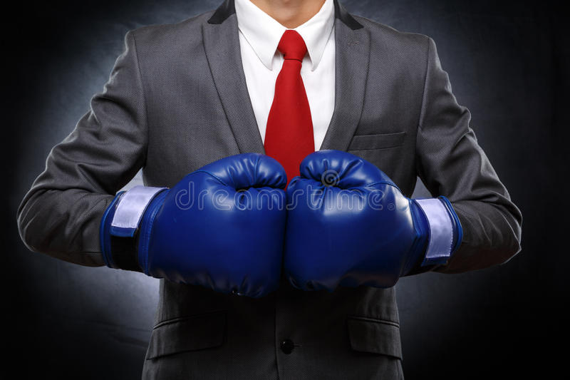 Business man in blue boxing gloves. On dark background . Detail of torso royalty free stock image