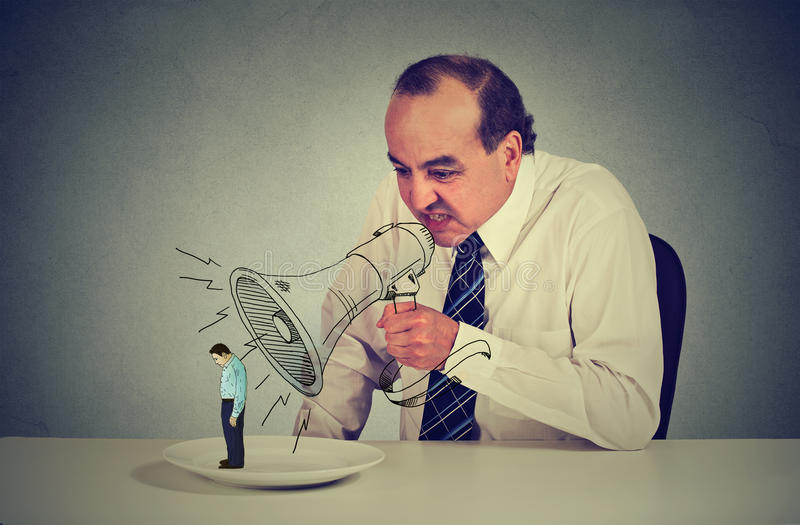 Business man boss screaming through megaphone at young scared colleague. Standing on a plate at his desk. Negative emotion bad business communication. Stressful stock photography