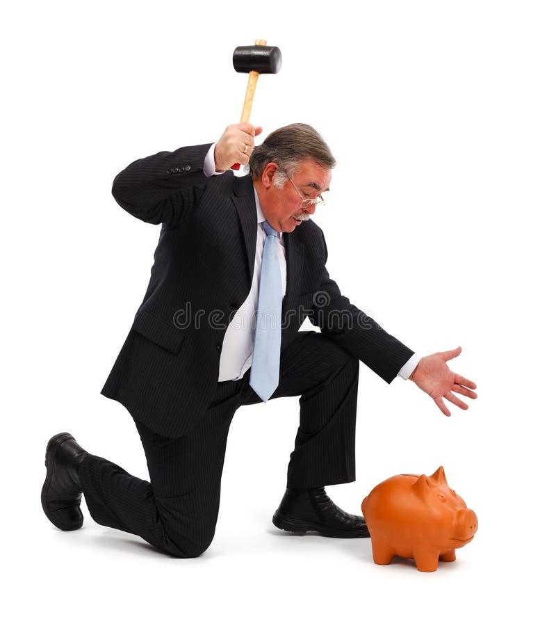Business man breaking piggy bank royalty free stock photos