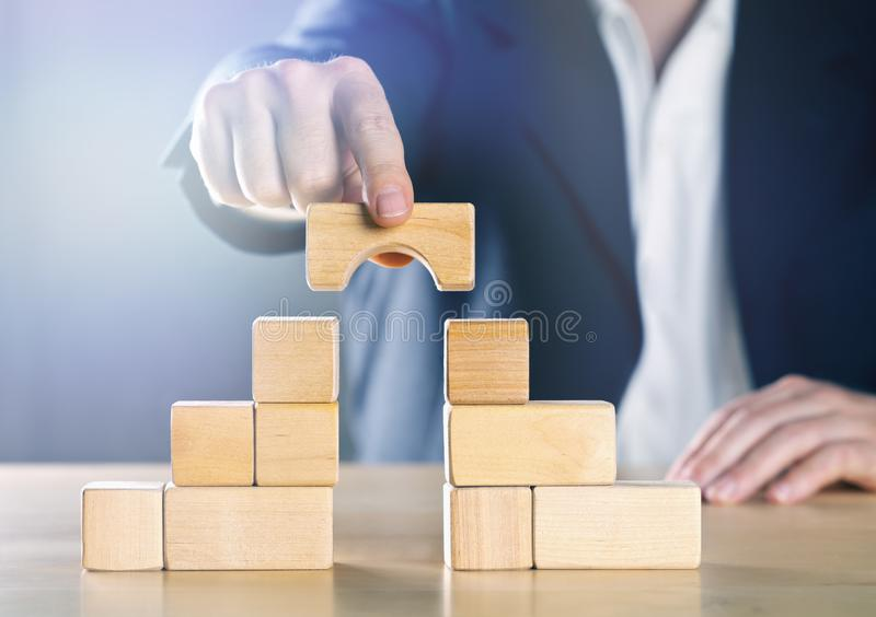 Business man bridging the gap between two towers or parties made from wooden blocks; conflict management or mediator concept royalty free stock images
