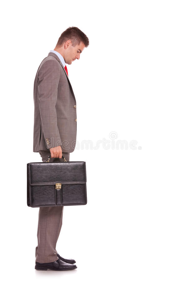 Business man with briefcase looking down. Side view of a young business man holding a briefcase and looking down - full body picture royalty free stock photography