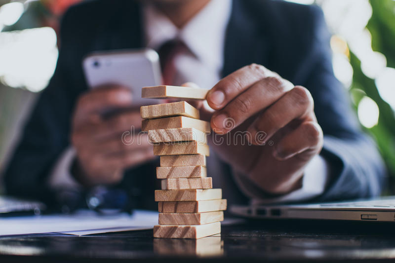 Business man building domino tower  royalty free stock photos