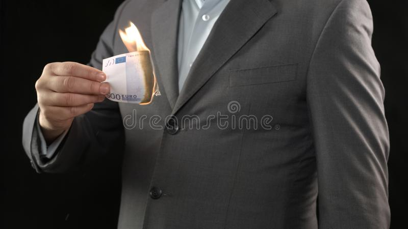 Business man burning five hundred euro bill, money wasting, bankruptcy concept. Stock photo royalty free stock image