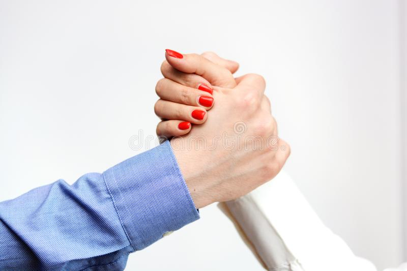 Business man and business woman shaking hands suggesting gender equality at the office stock images