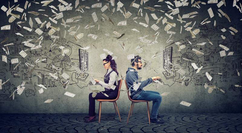 Business man and businesswoman working on computer developing successful strategy under money rain. Businessman and businesswoman working on computer developing royalty free stock photo