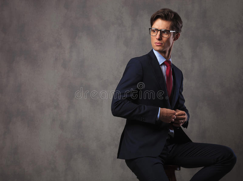 Business man buttoning his suit and looks over his shoulder stock photos
