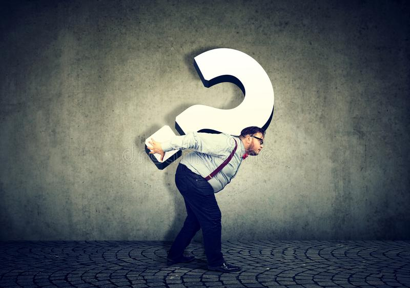 Business man carrying big question mark. Overworked chubby young business man carrying big question mark on his back royalty free stock image