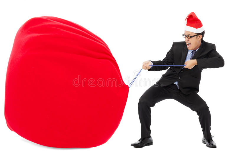 Business man carrying a heavy gift sack with christmas hat. Isolated on white background stock photo