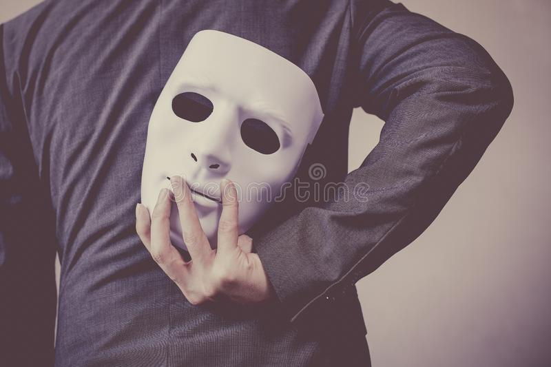Business man carrying white mask to his body indicating Business fraud and faking business partnership.  royalty free stock photos