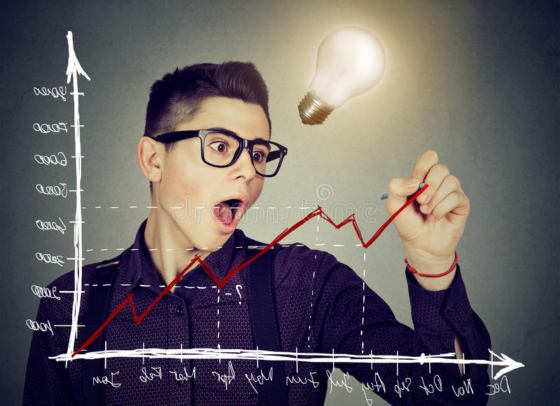 Business man charting a positive trend graph has bright idea. Young business man charting a positive trend graph has bright idea royalty free stock photography