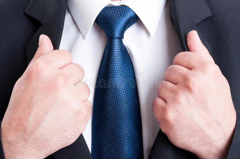 Business man chest as powerful leader concept. Black suit, white shirt and blue tie stock photography