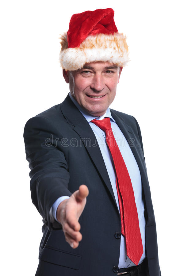 Business man in christmas hat welcomes you with a hand shake stock image