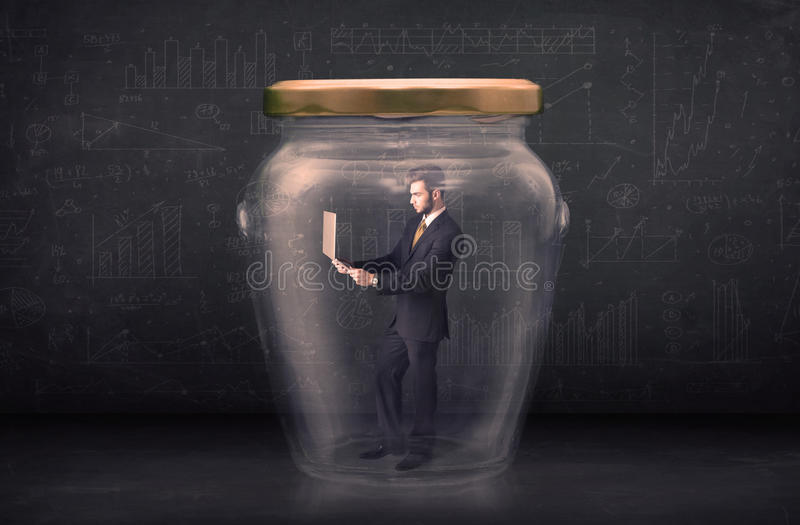 Business man closed into a glass jar concept stock photography