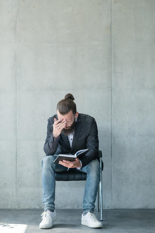 Business man concentrated reading notepad fatigue. Business man concentrated on reading data from notepad. fatigue headache tiredness and overworking royalty free stock photo
