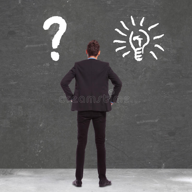 Business man between confusion and a great idea. Back picture of a business man between confusion and a great idea royalty free stock photos