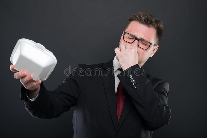 Business man covering nose from bad smelling lunchbox stock photo