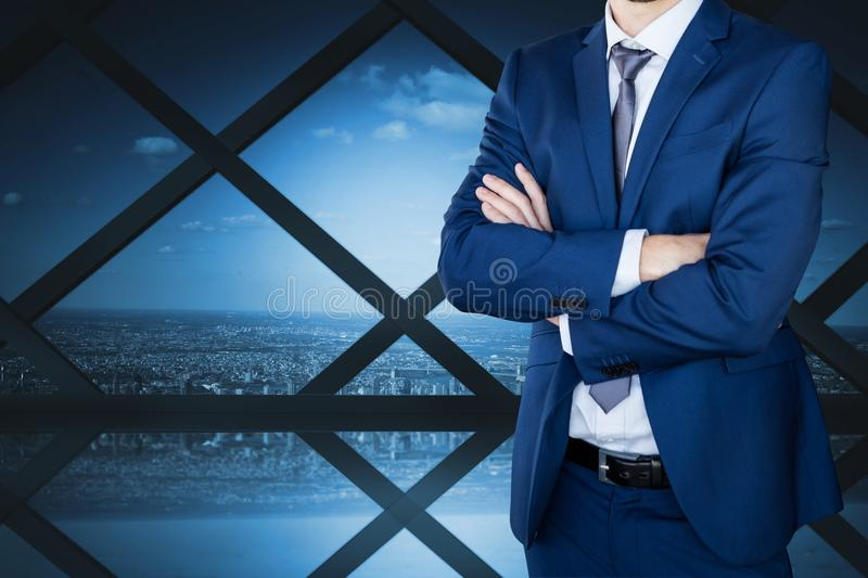 Business man with crossed arms against cityscape background stock image
