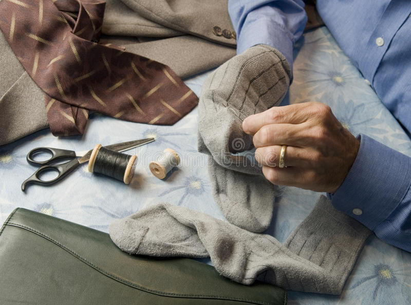 Business man darning socks stock photos